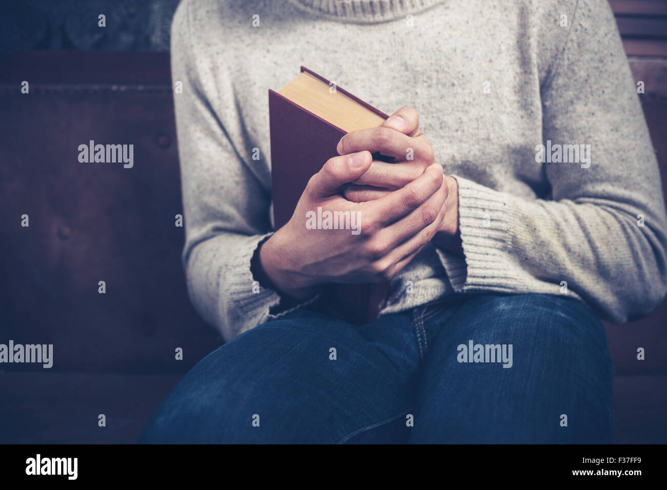 Nervous young man sitting on a sofa is clutching a book - Stock Image