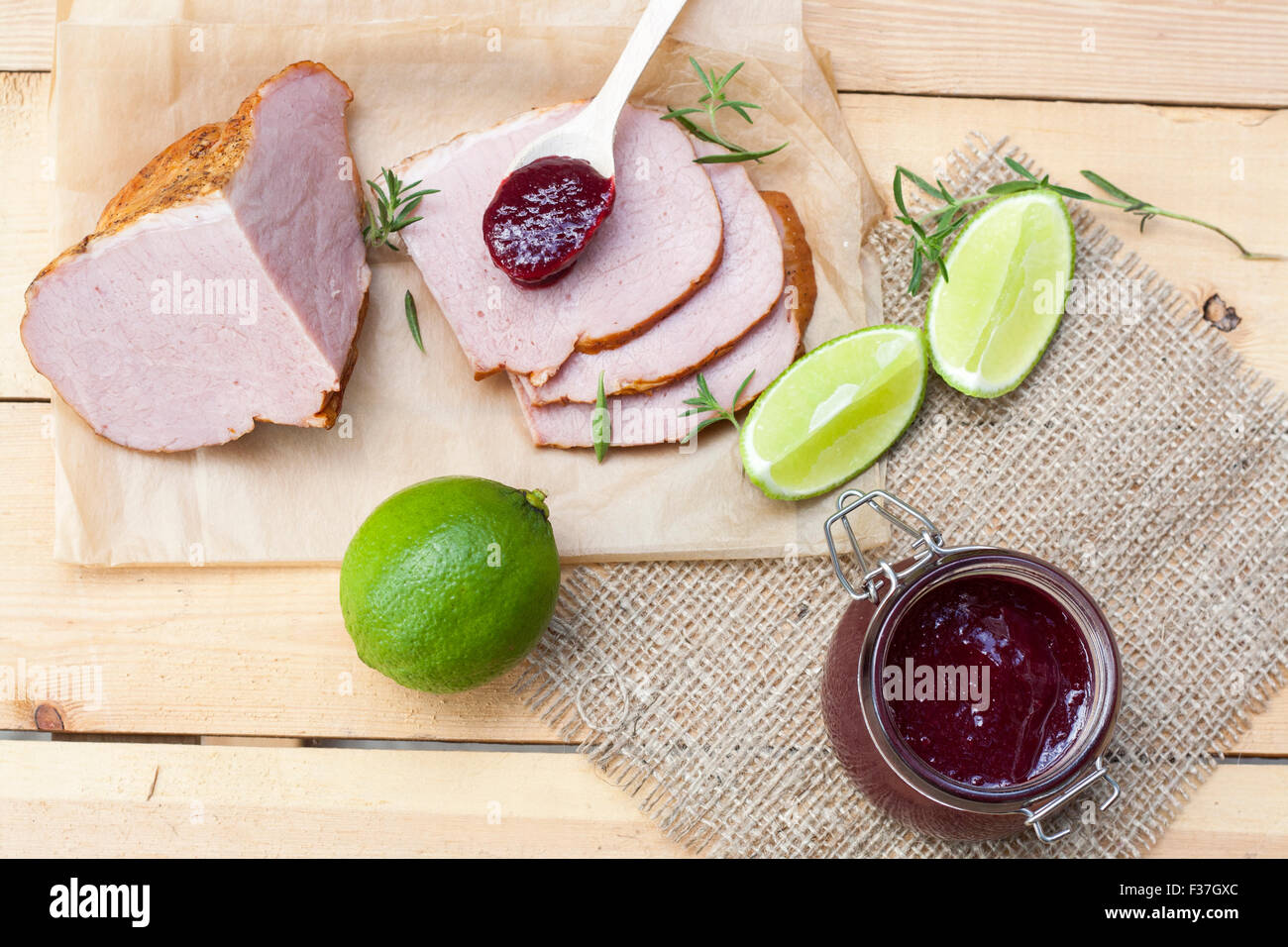 Home made organic cherry jam confiture, smoked meat, rosemary and lime on a wooden table - Stock Image