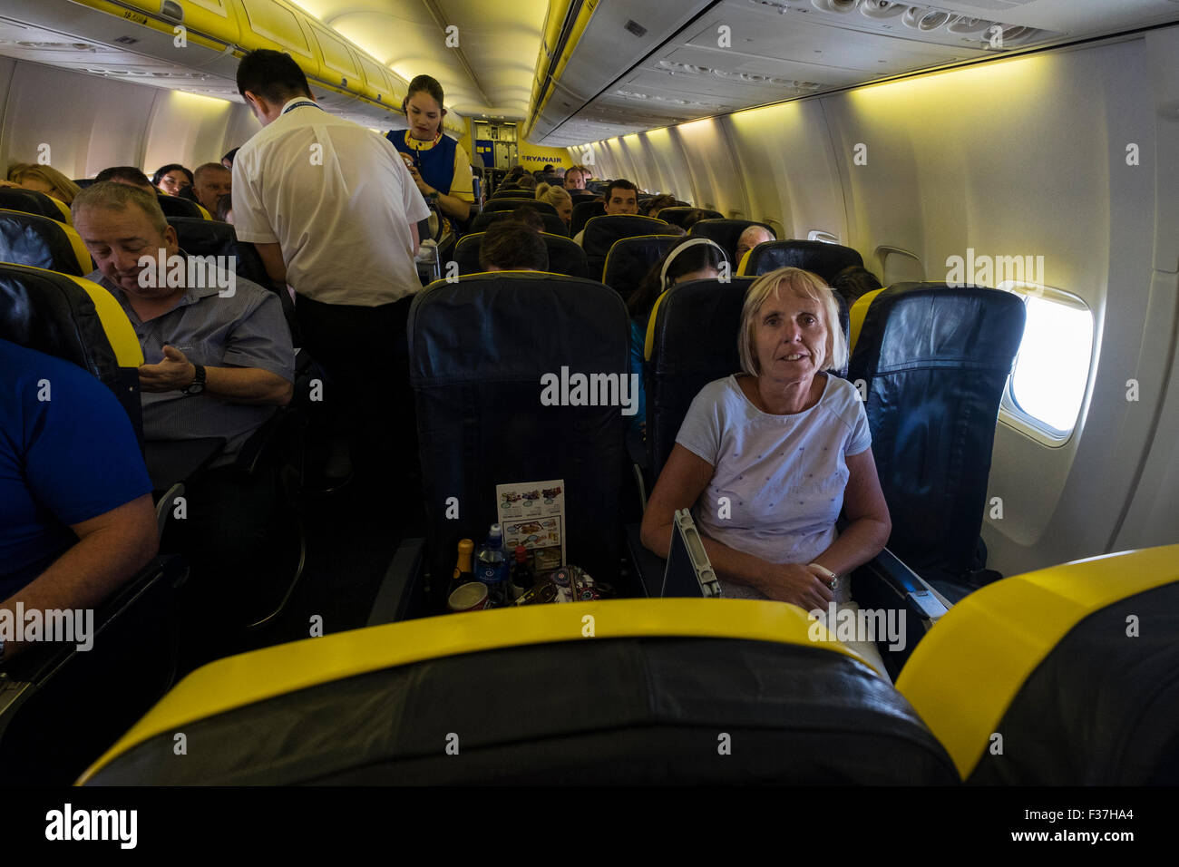 Passengers and cabin crew on a Ryanair Airbus A380 flight. - Stock Image