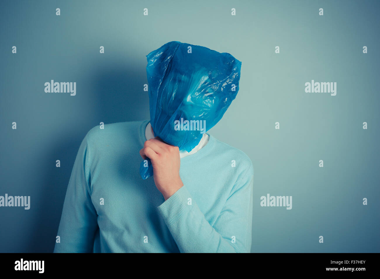 A man with a plastic bag over his head is suffocating - Stock Image