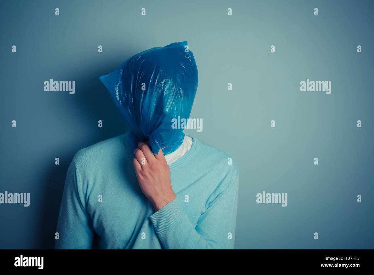 A man is wearing a plastic bag over his head - Stock Image