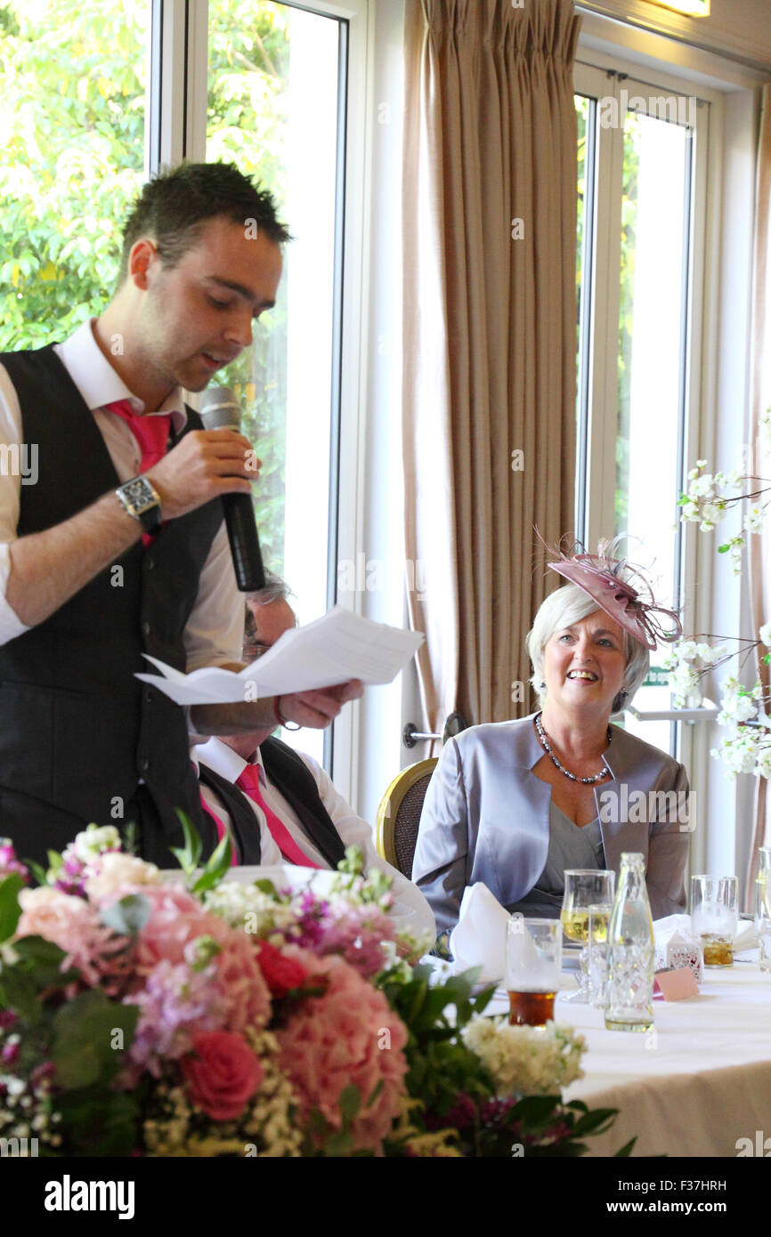 Proud mother watches as her son gives a wedding speech, UK - Stock Image
