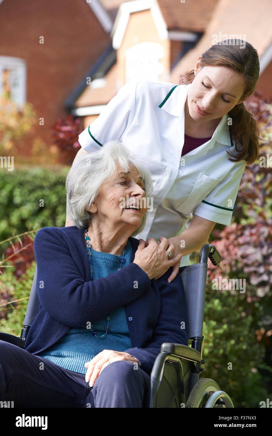 Carer Pushing Senior Woman In Wheelchair - Stock Image
