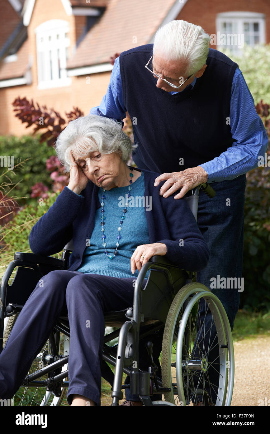 Depressed Senior Woman In Wheelchair Being Pushed By Husband - Stock Image