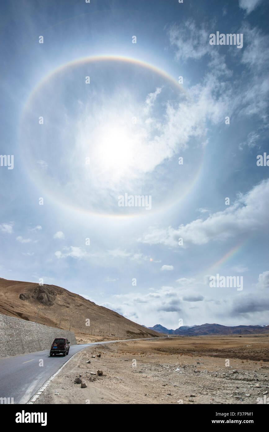 Circular rainbow with secondary rainbow on a road trip through Tibet. - Stock Image