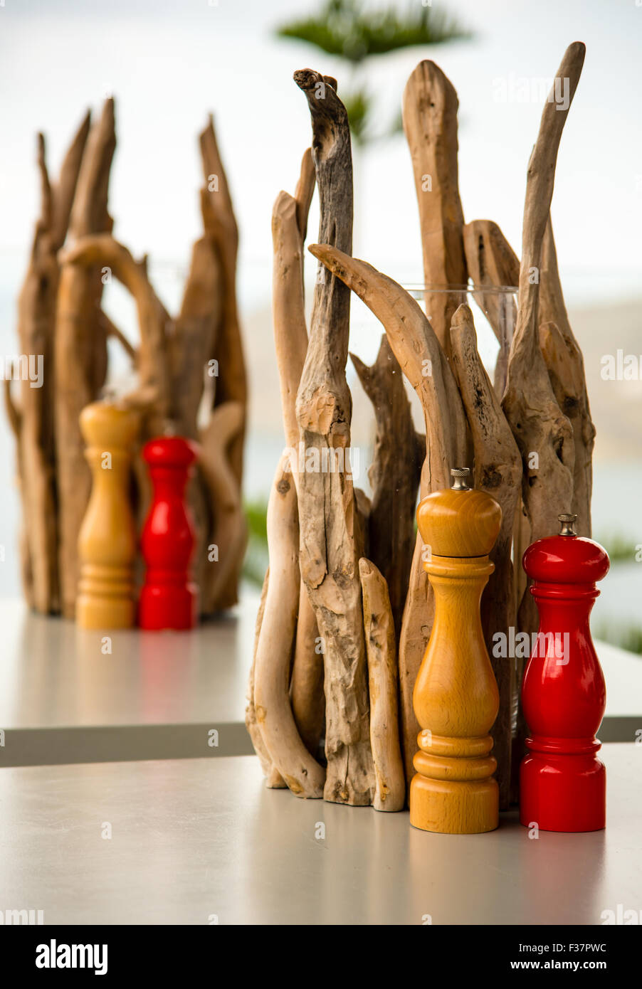 wooden salt and pepper mills on a dinner table - Stock Image