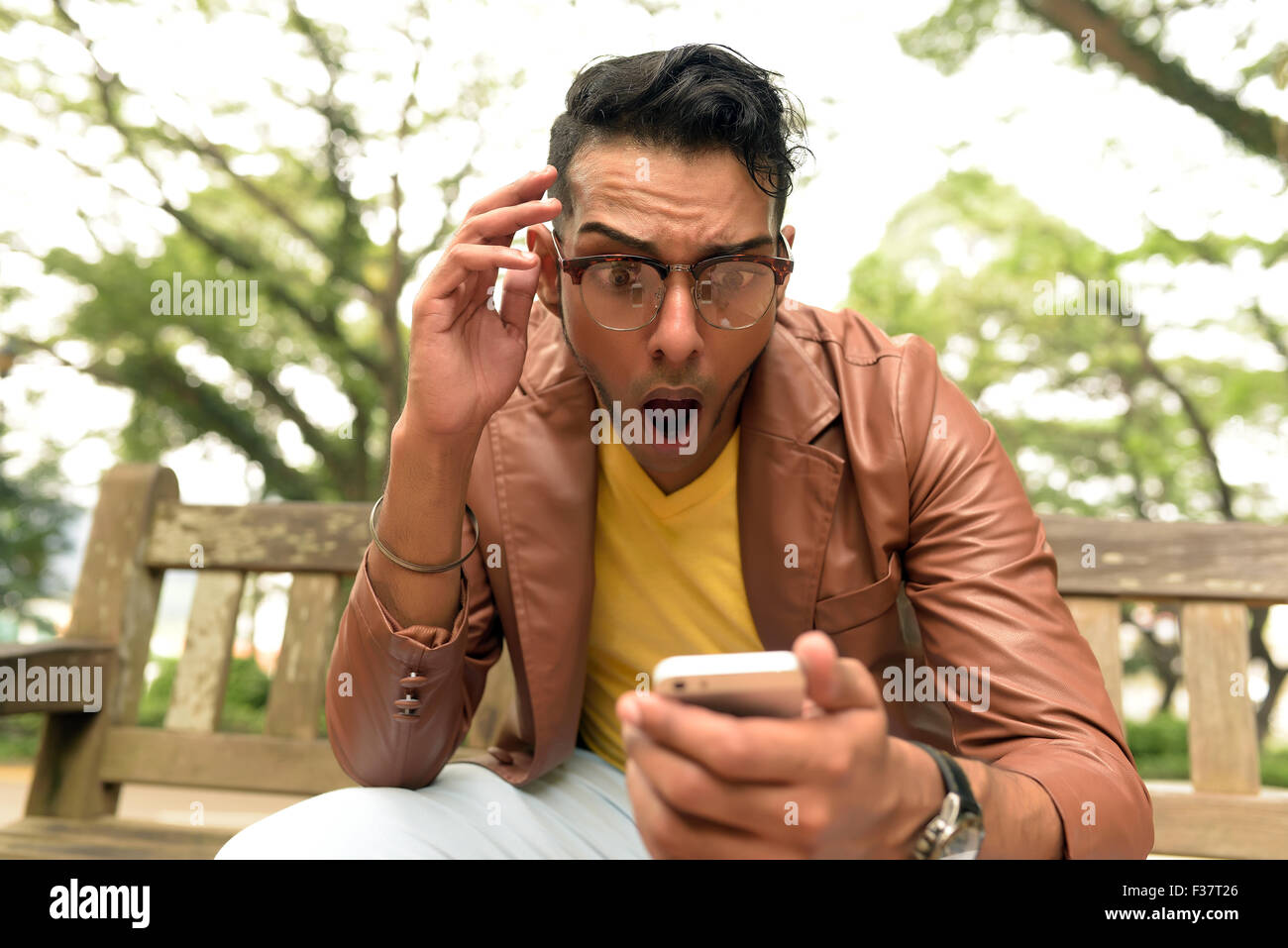 Asian , Man , Indian Ethnicities , Smart Phone , Casual Clothing , Outdoor . Stock Photo