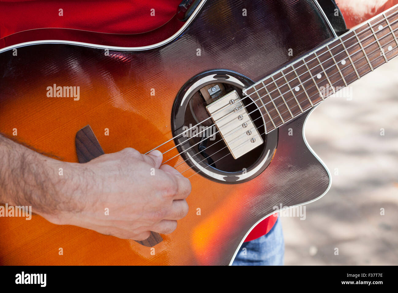 Man playing acoustic-electric guitar - USA - Stock Image