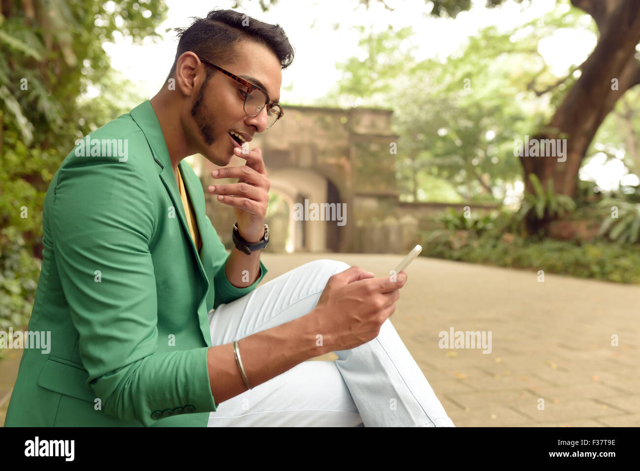 Asian , Man , Indian Ethnicities , Smart Phone , Casual Clothing , Outdoor . - Stock Image