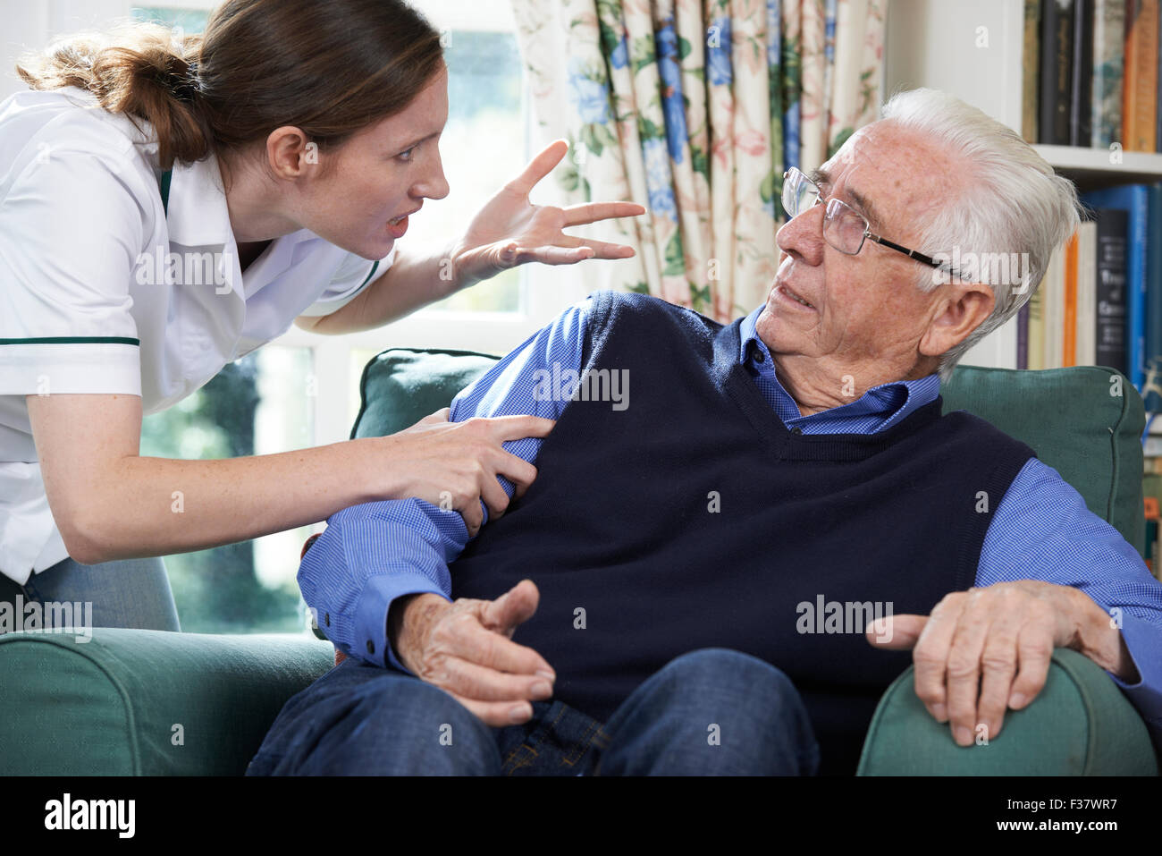 Care Worker Mistreating Senior Man At Home - Stock Image