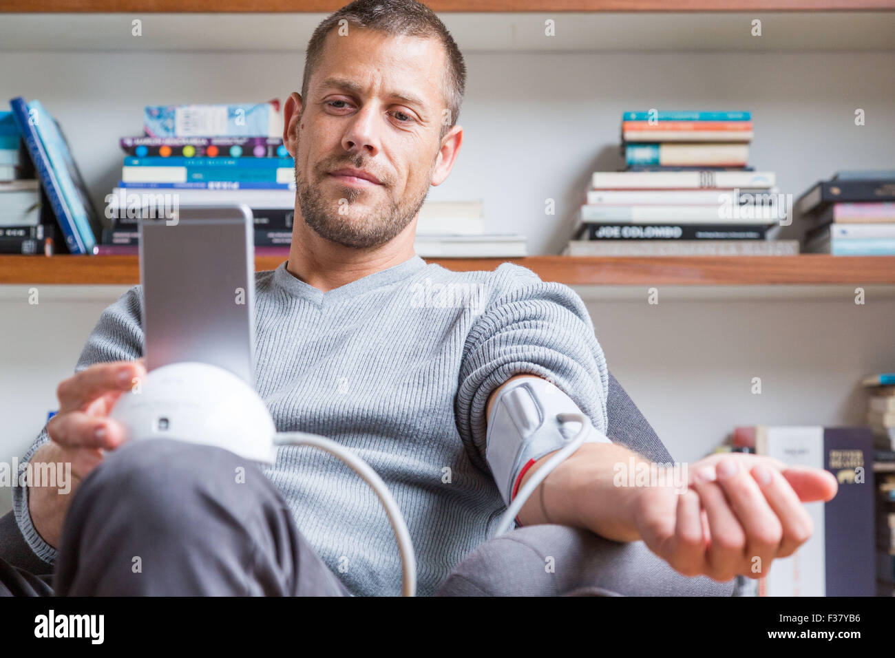 Man taking his blood pressure with a sphygmomanometer connected to his cell phone. - Stock Image