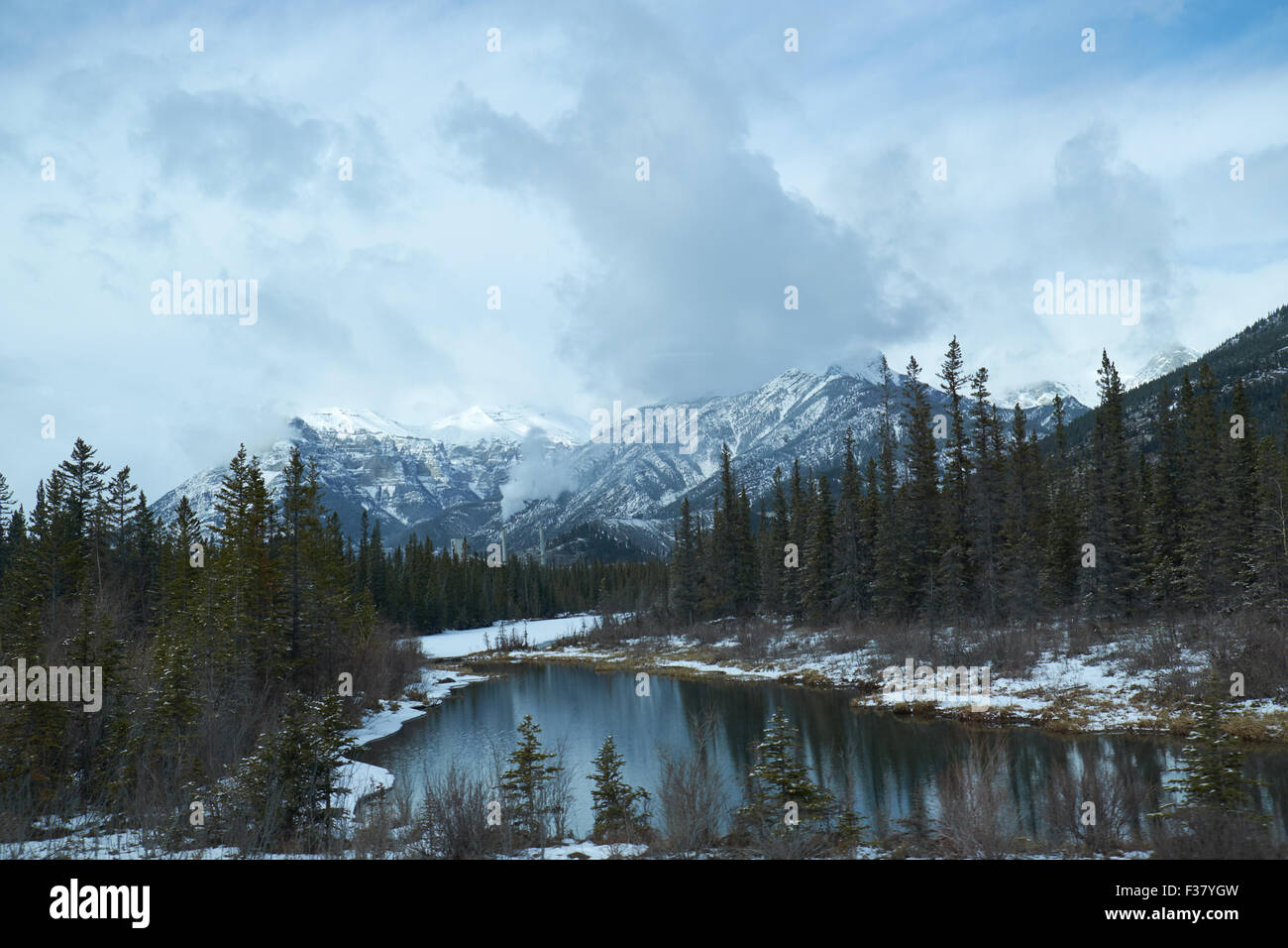 Canadian winter landscape with the Rockies Mountains and a lake with reflections - Stock Image