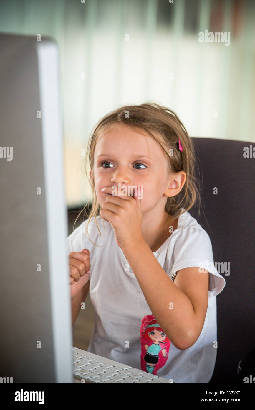 5 year old girl using a computeur. - Stock Image