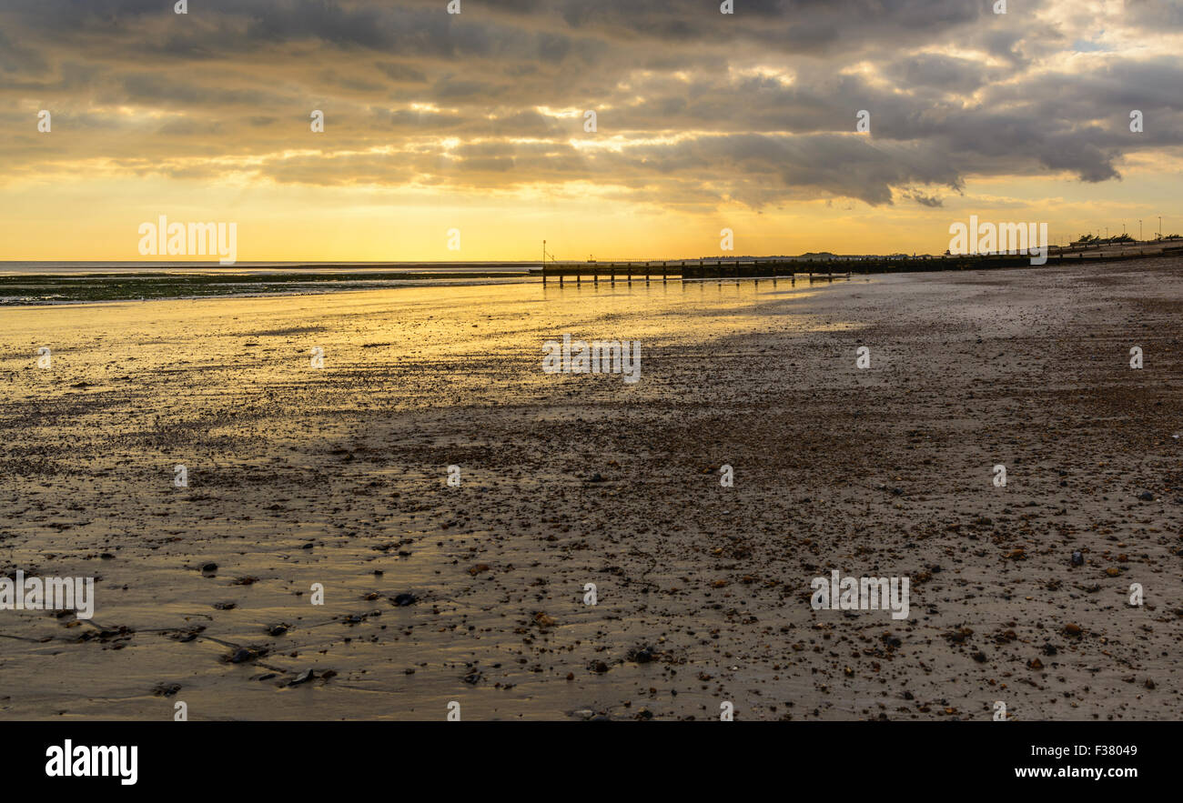 Deserted beach at low tide in early evening after the sun has set.in England, UK. - Stock Image