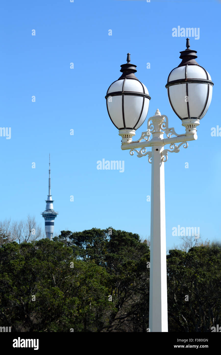 An old street lamp in the foreground against the Sky tower in the background in Auckland, New Zealand. copy space - Stock Image