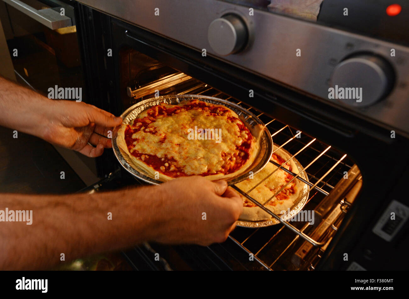 Man hands getting out from the oven a ready homemade pizza. - Stock Image
