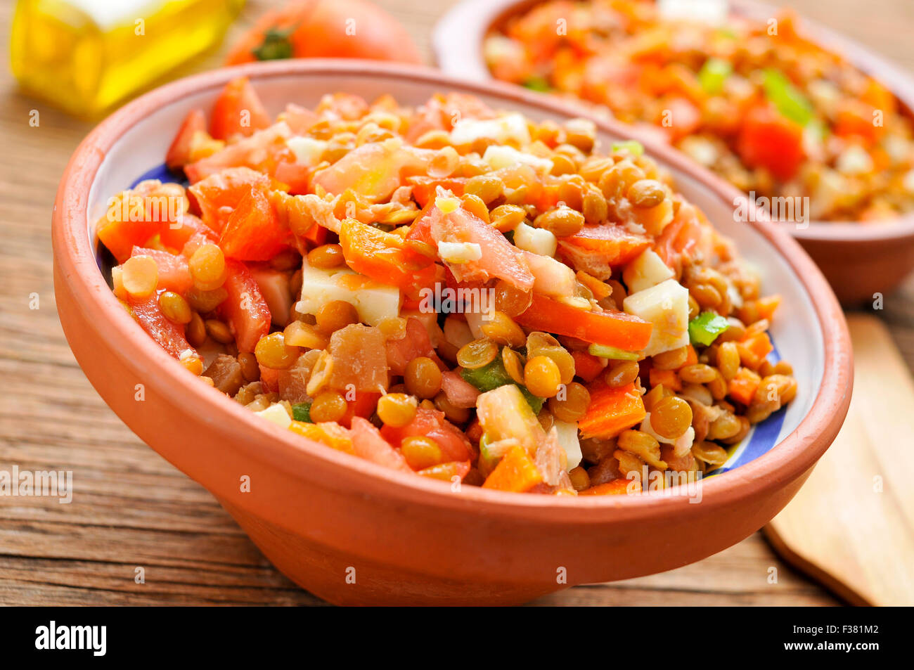 closeup of a earthenware bowl with a lentil salad on a rustic wooden table - Stock Image