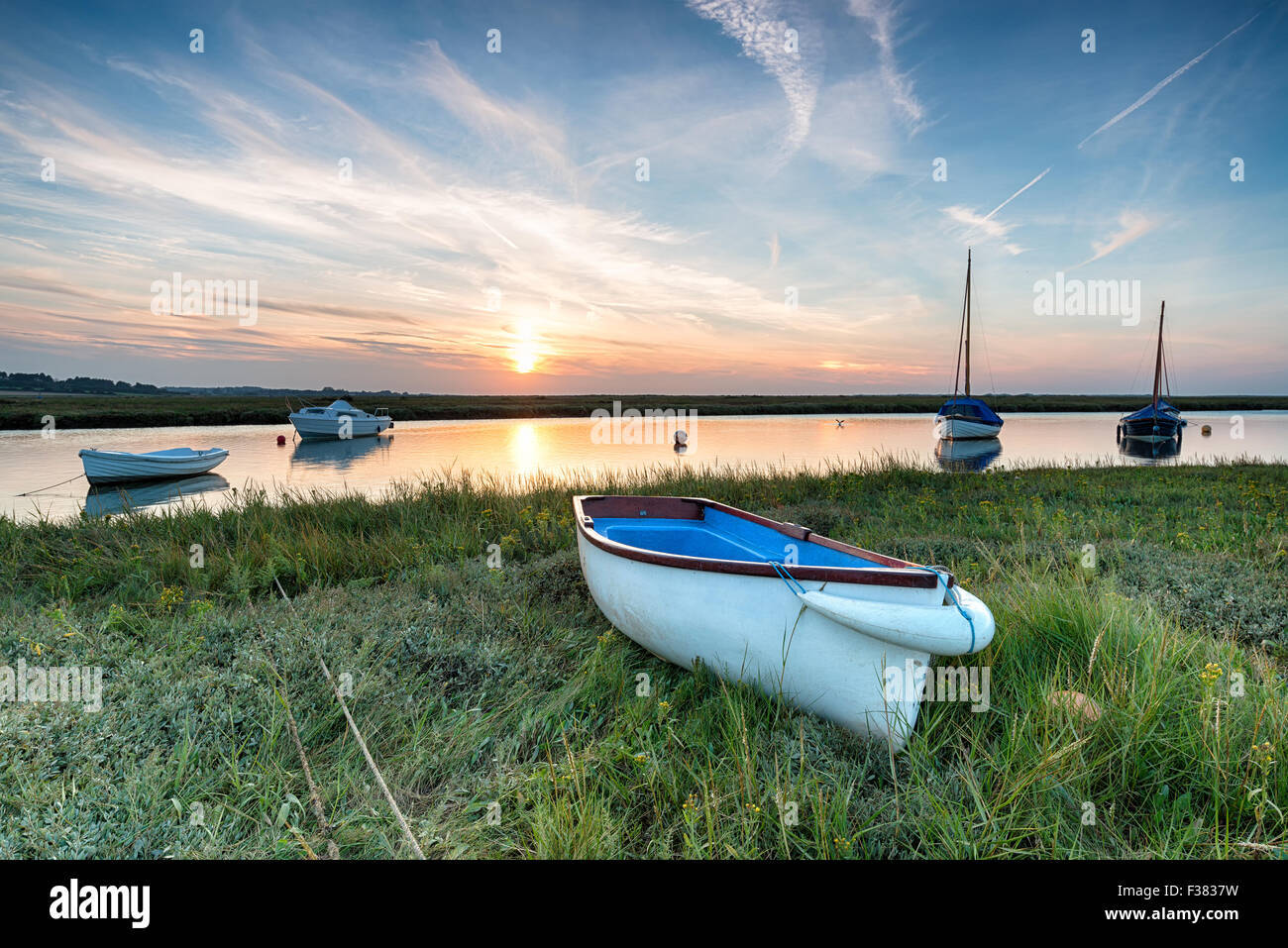 Sunset over boats on the salt marshes at Blakeney on the north coast of Norfolk - Stock Image