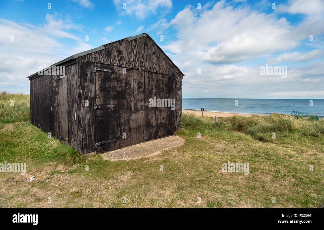 Black hut on the beach at Winterton on Sea on the Norfolk coast - Stock Image