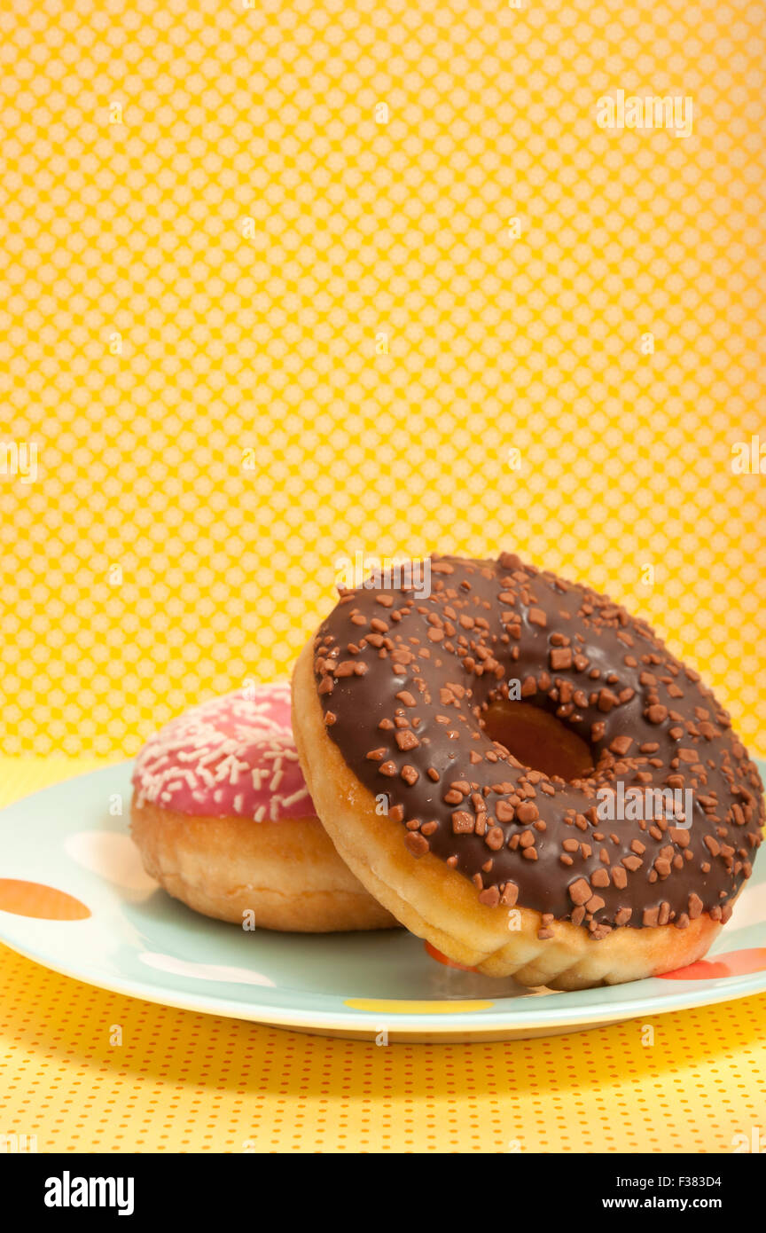 glazed doughnuts on a plate - Stock Image
