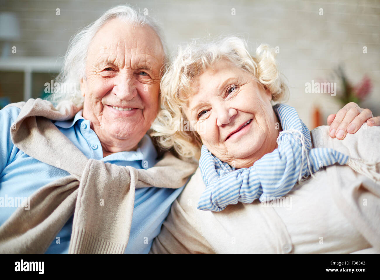 Affectionate elderly couple looking at camera with smiles - Stock Image
