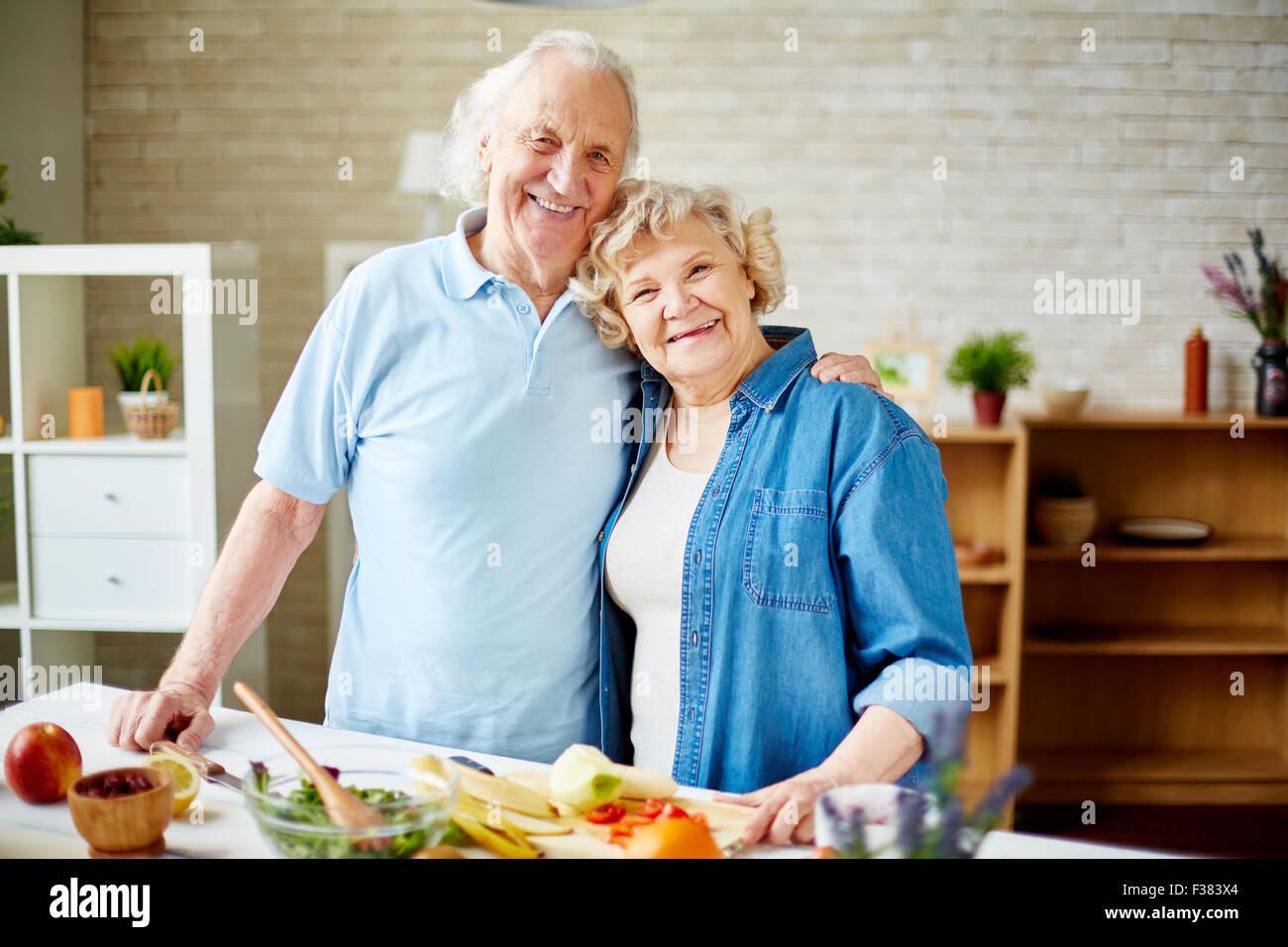 Cheerful seniors standing by table with fruits and looking at camera in the kitchen - Stock Image