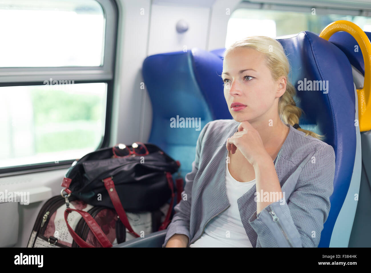 Blonde caucasian business woman traveling by train. Business travel concept. - Stock Image