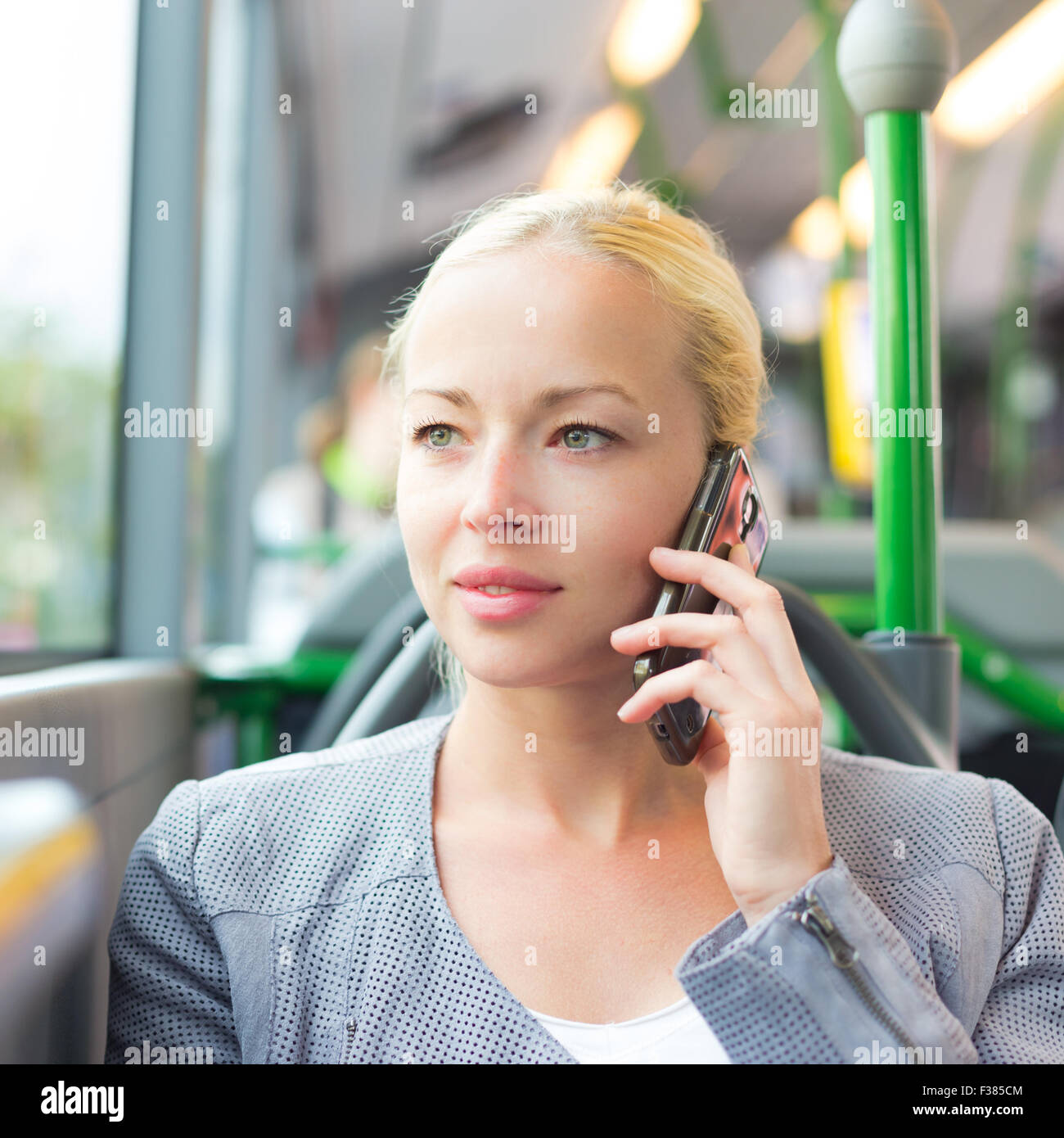 Blonde caucasian business woman talking on cell phone, traveling by bus. Public transport and commuting to work. Stock Photo