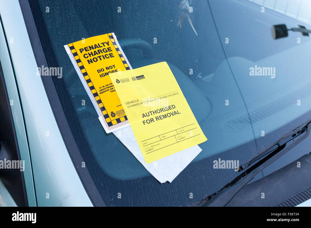 Illegal parking: Parking ticket or Penalty Charge notice with Authorised For Removal notice added on a windscreen, - Stock Image