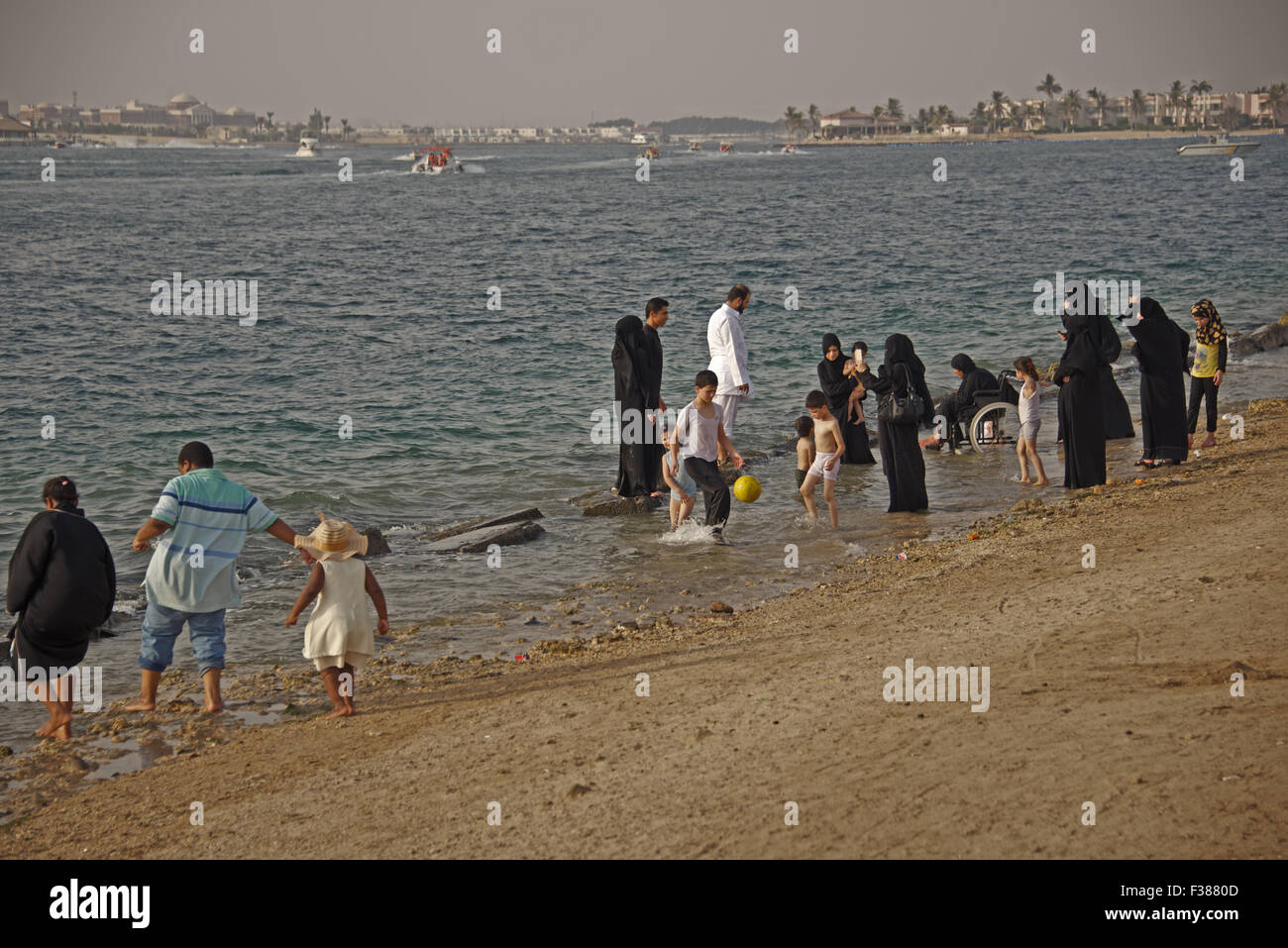 A typical scene at the Corniche in Jeddah, Saudi Arabia. Families stroll the beach of the Red Sea, pray and watch - Stock Image