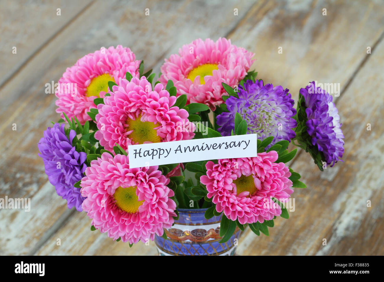 Happy Anniversary card with colorful aster flowers bouquet on rustic ...