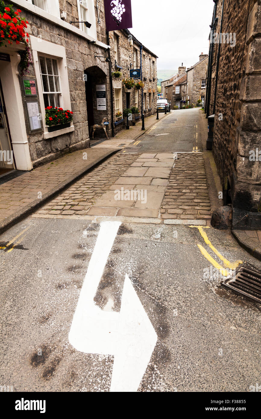 Kirkby Lonsdale Village UK left hand turn arrow painted on road town houses homes narrow street Yorkshire England - Stock Image