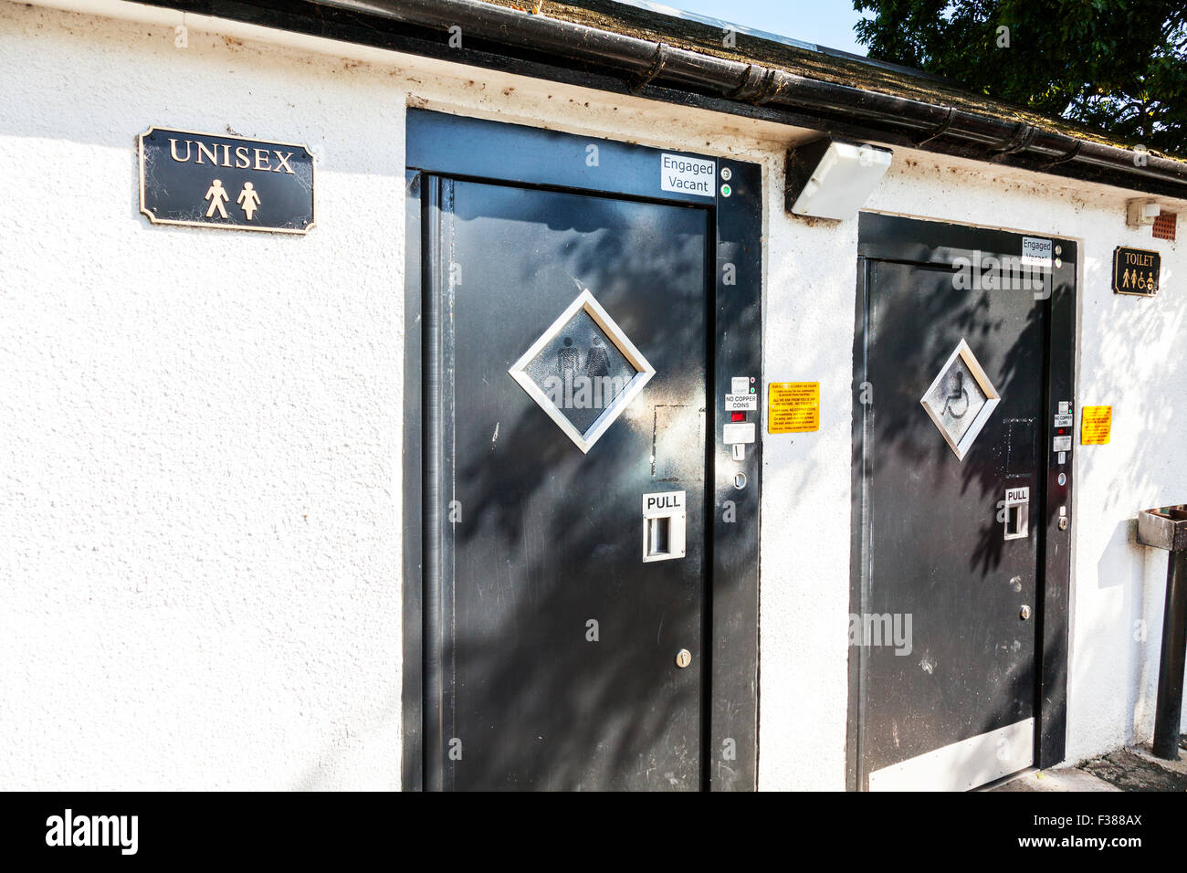 unisex toilet toilets pay payment needed to spend penny shared convenience conveniences Kirkby Stephen Yorkshire - Stock Image