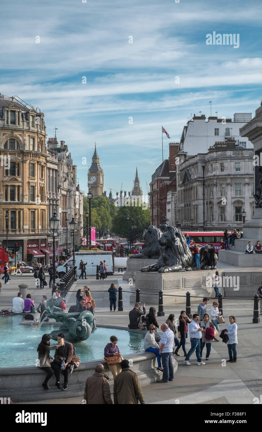Tourists in Trafalgar Square, with Lions and Big Ben in the background, Westminster, London, England UK - Stock Image