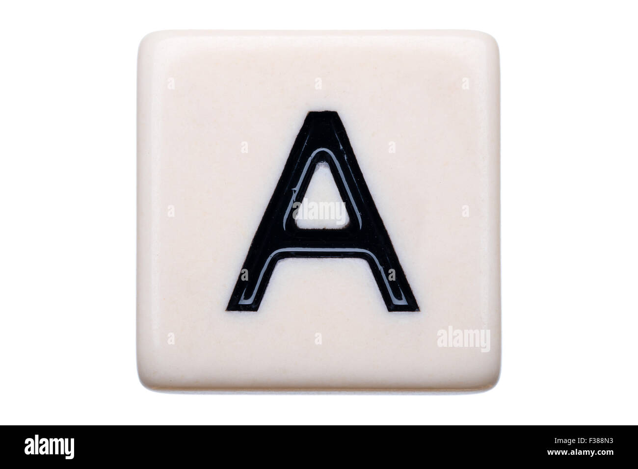 A macro shot of a game tile with the letter A on it on a white background. - Stock Image