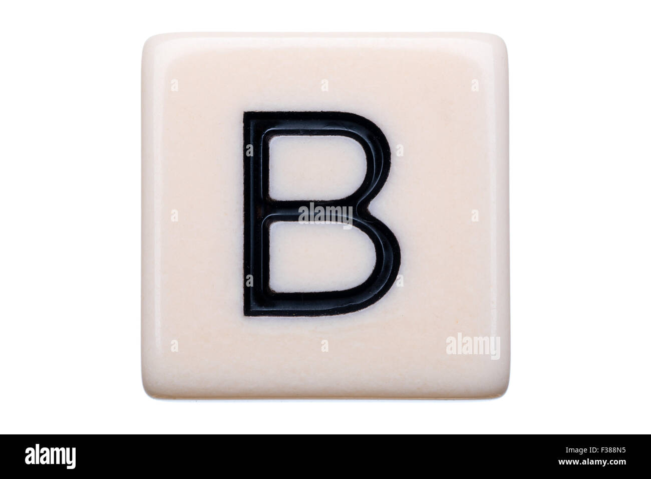 A macro shot of a game tile with the letter B on it on a white background. - Stock Image