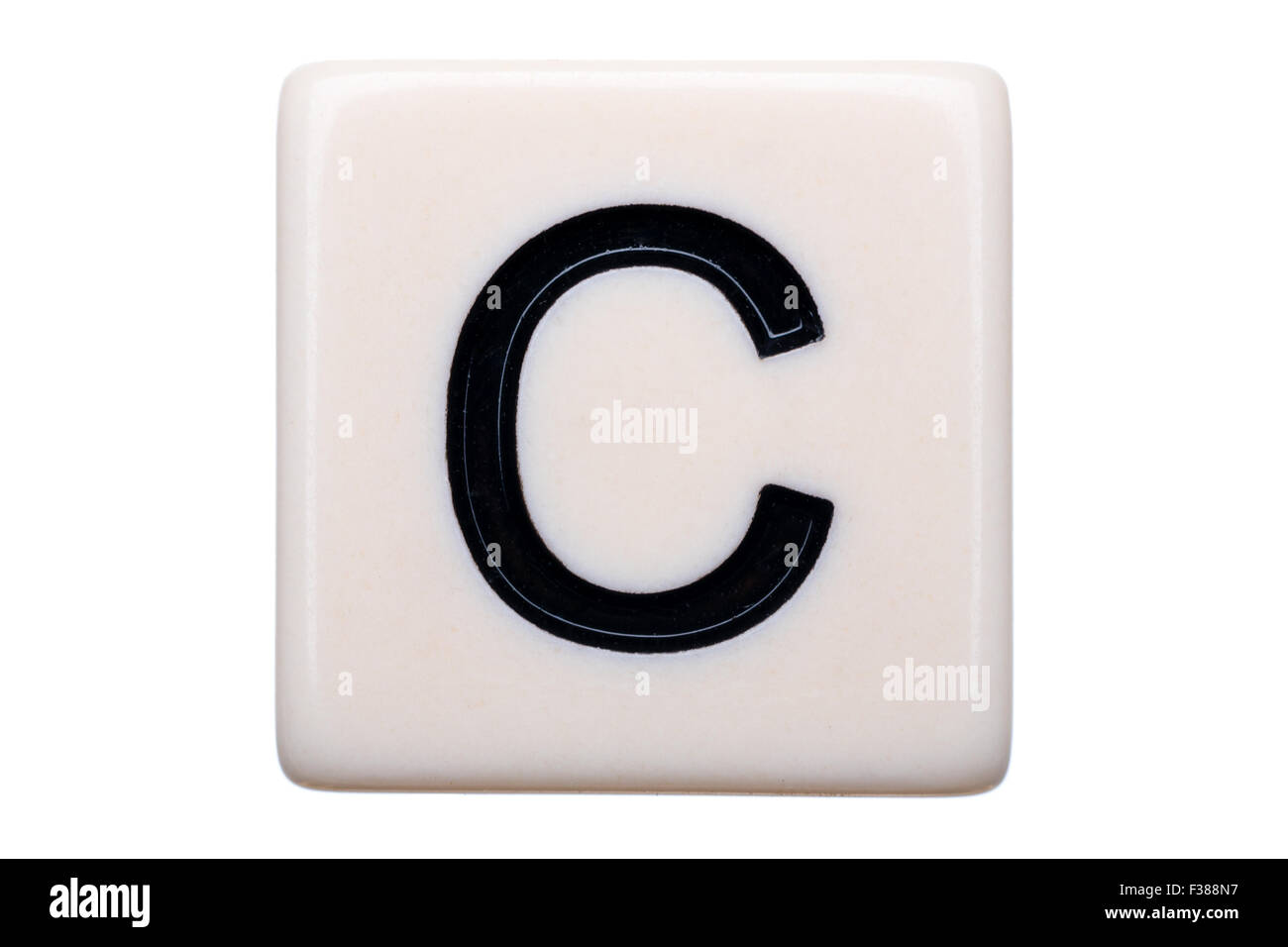 A macro shot of a game tile with the letter C on it on a white background. - Stock Image