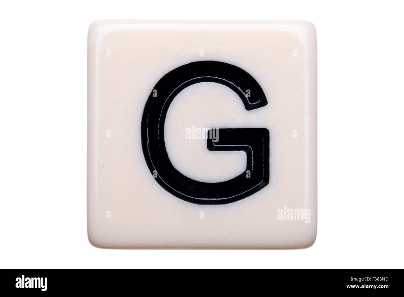A macro shot of a game tile with the letter G on it on a white background. - Stock Image