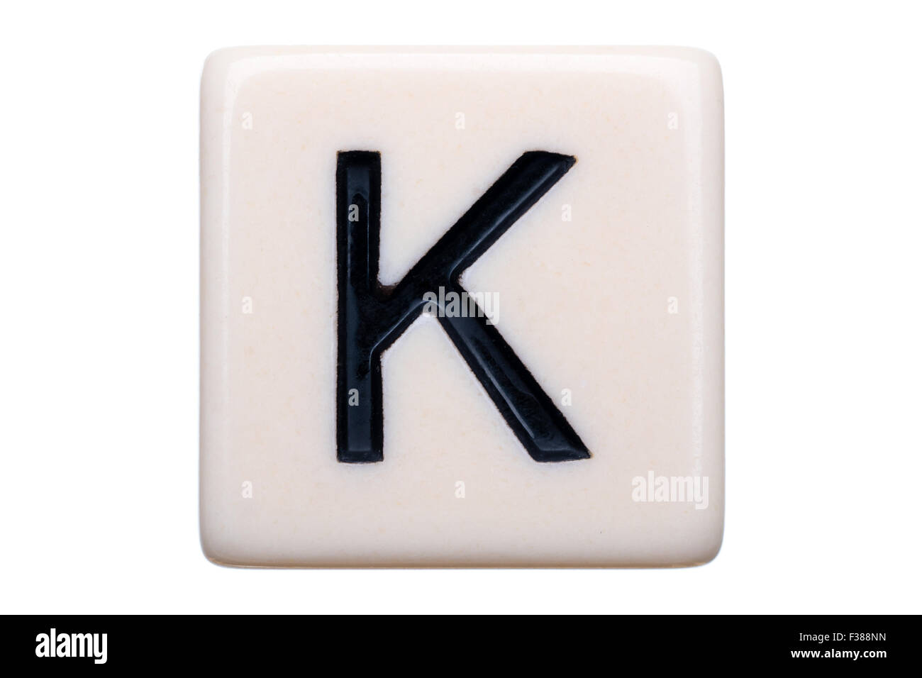 A macro shot of a game tile with the letter K on it on a white background. - Stock Image