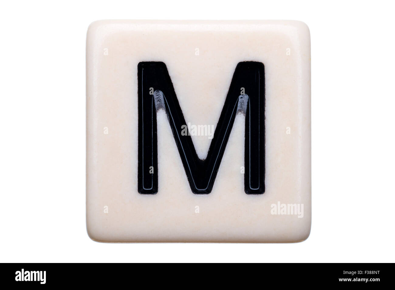 A macro shot of a game tile with the letter M on it on a white background. - Stock Image
