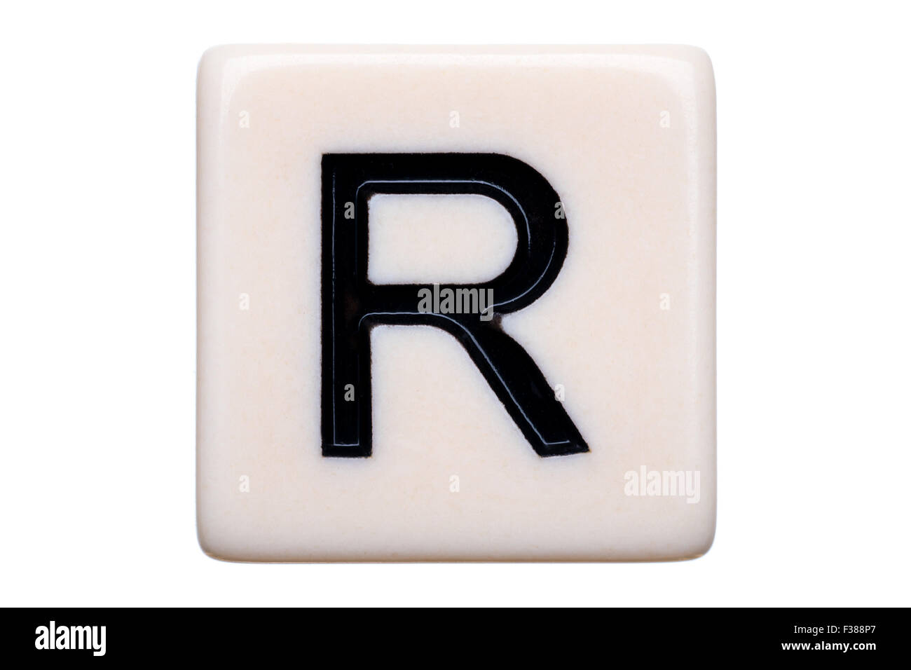 A macro shot of a game tile with the letter R on it on a white background. - Stock Image