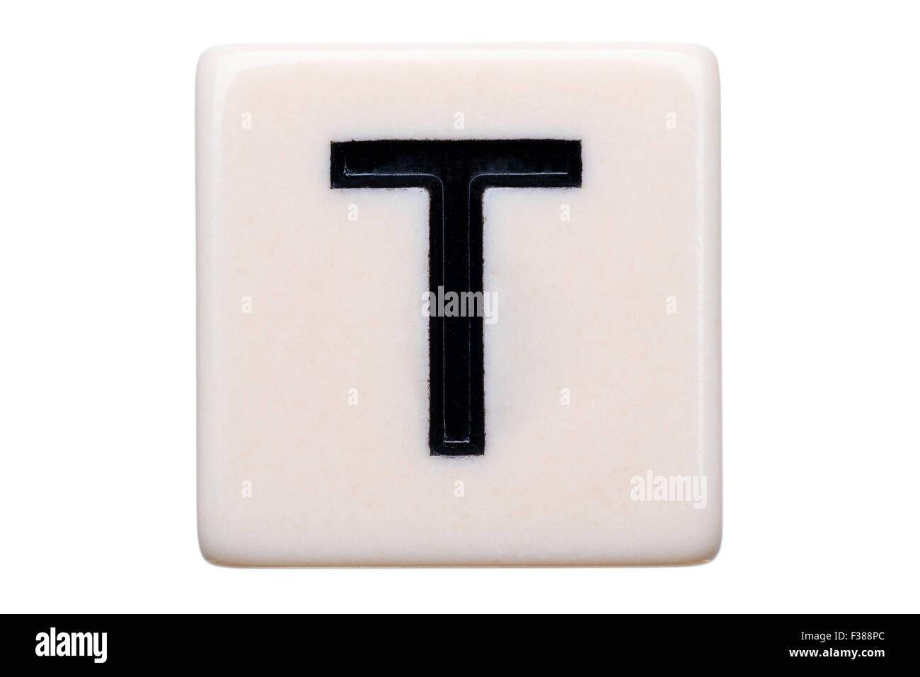 A macro shot of a game tile with the letter T on it on a white background. - Stock Image
