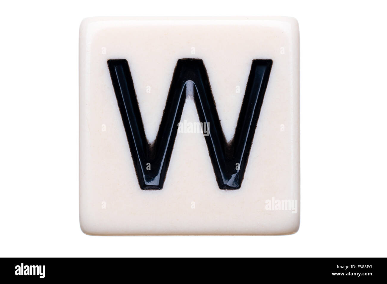 A macro shot of a game tile with the letter W on it on a white background. - Stock Image