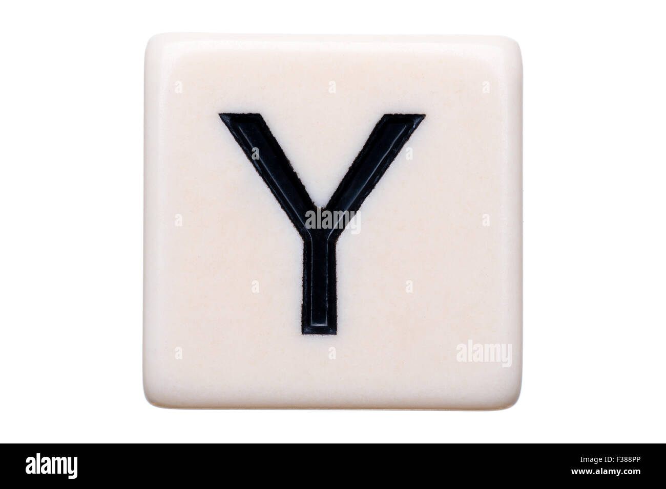 A macro shot of a game tile with the letter Y on it on a white background. - Stock Image