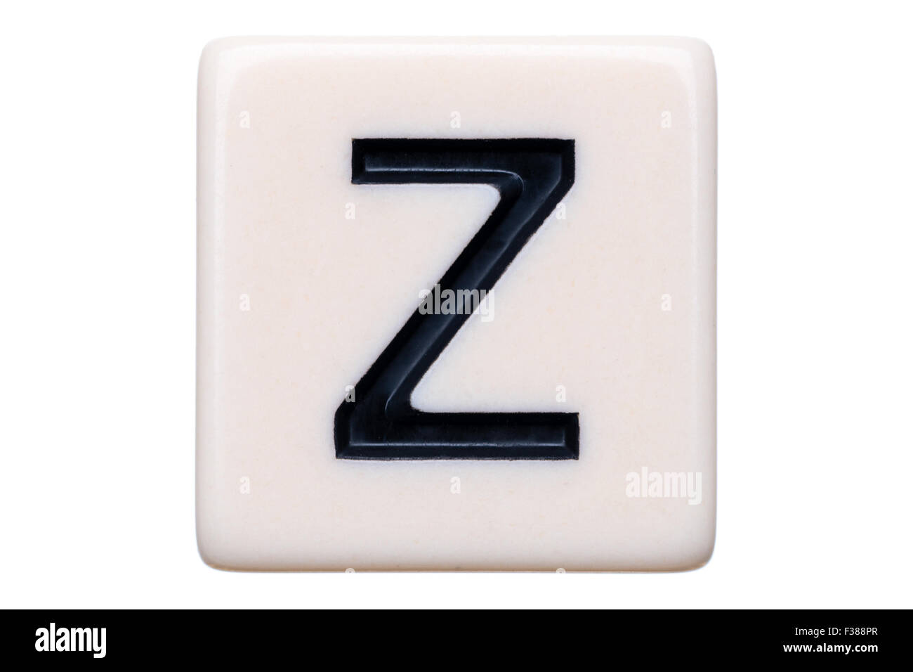 A macro shot of a game tile with the letter Z on it on a white background. - Stock Image