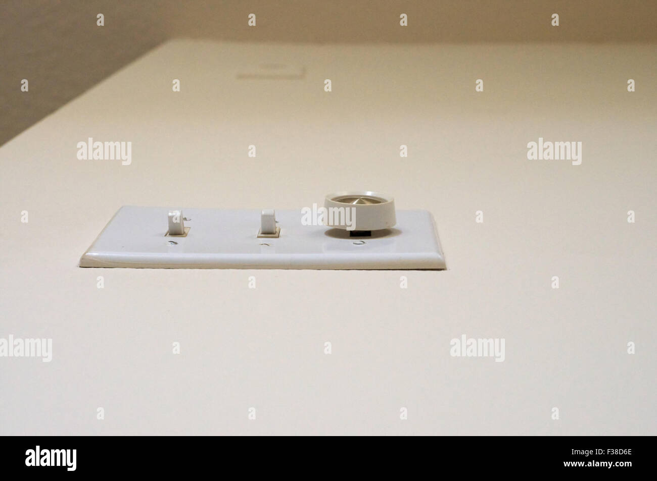 Looking up from the floor at a bank of light switches, two toggle switches, and one dimmer knob on empty light colored - Stock Image