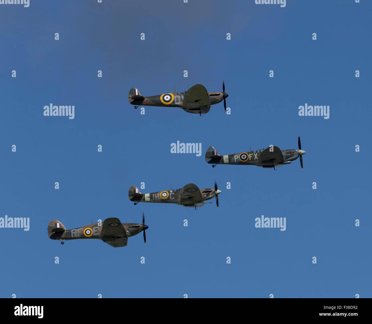 Three Spitfire and one Hurricane fighter aircraft at the Battle of Britain 75th Anniversary Flypast  at Goodwood - Stock Image