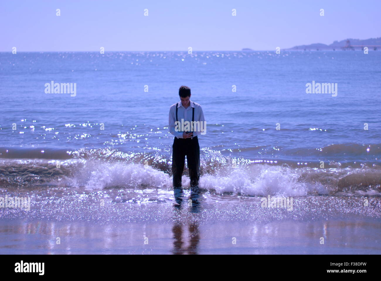 man standing in the water in the ocean waves holding a little boat Stock Photo