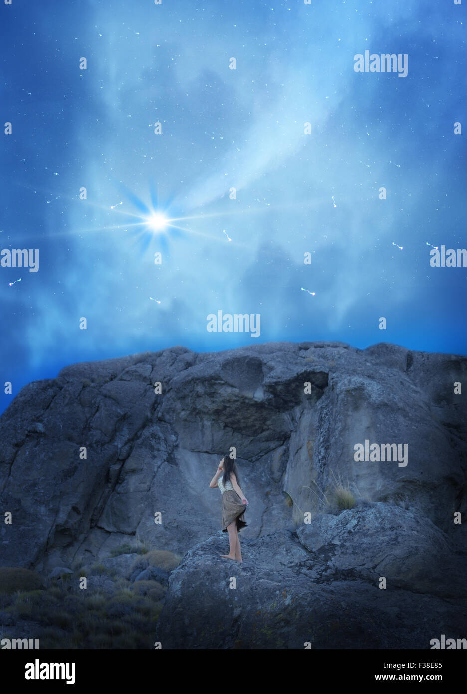 girl in dress stand up in a mountain while she sees the sky Shooting Star - Stock Image