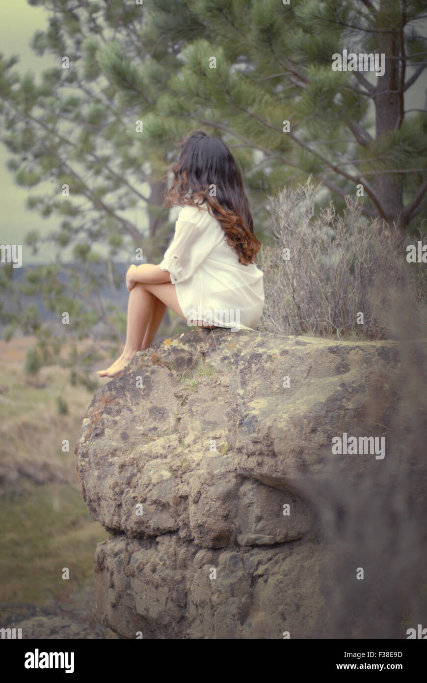 cute girl sitting in a big stone in the forest - Stock Image